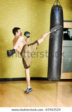 Kickboxer working out on punching bag - stock photo