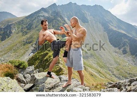 Kickboxers or muay thai fighters training in the mountains, sparring - stock photo