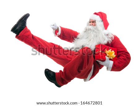 Kickboxing Santa Claus flying isolated on white background. Aggressive Santa Claus jumps with feet kick. Fighting Santa Claus with a gift. Attack Santa Claus with a kick jump on white background. - stock photo