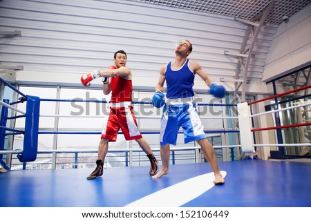 Kickboxing. Two kickboxers fighting on the boxing ring - stock photo