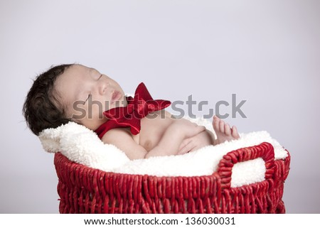 Kicking back.  Adorable biracial newborn fast asleep in a red basked wearing a red bowtie. - stock photo
