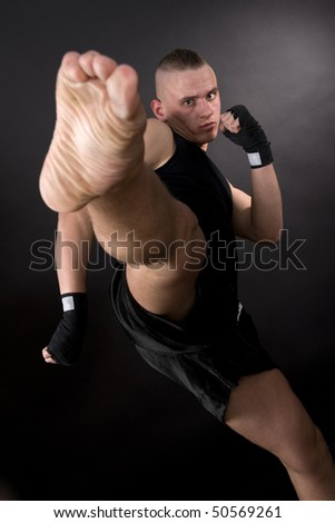 Kicking man with scar face in motion on dark background. Focus on face - stock photo