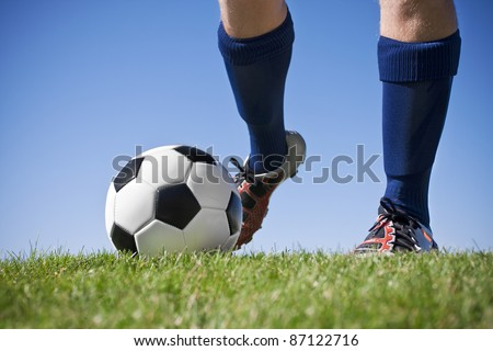 Kicking the soccer ball (close, low angle view) - stock photo