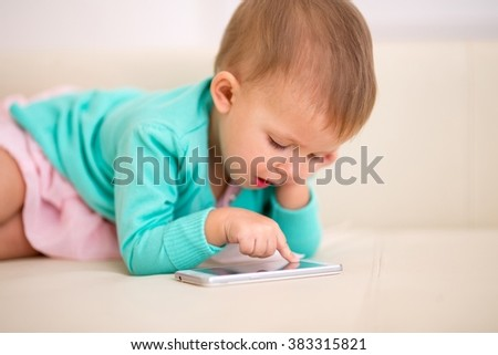 Kid and a half months of age playing in a smartphone. - stock photo