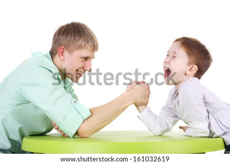 kid and adult brothers arm wrestling isolated on white - stock photo
