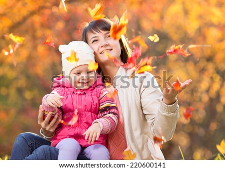 Kid and beautiful mother play and throw leaves outdoor in autumn park - stock photo