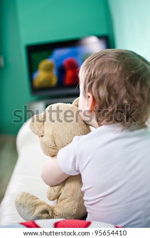 Kid and his teddy bear watching TV
