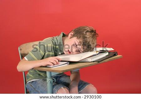 kid asleep at his desk - stock photo