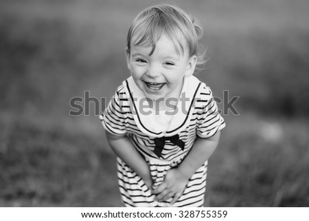 Kid at countryside wearing cute dress posing and laughing out loud.