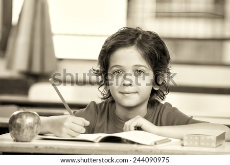Kid at school writing on his book with an apple on the desk. - stock photo