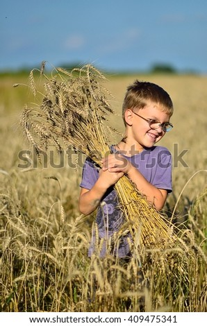 Kid at wheat field with boucket - stock photo
