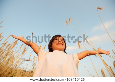 Kid at wheat field with open arms - stock photo