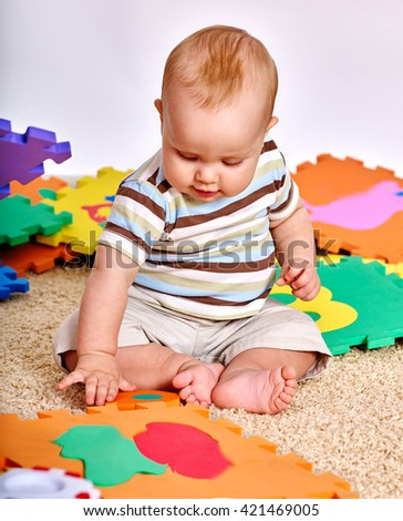 Kid baby boy sitting on floor and playing with baby puzzle toy.