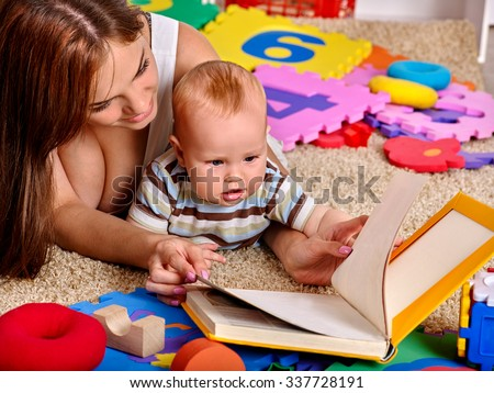 Kid baby boy with mother lying on floor and reading book at home.  - stock photo