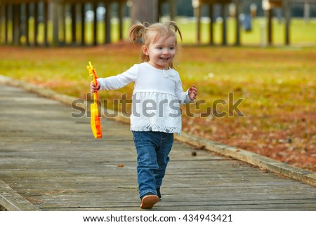 Kid baby girl with toy guitar walking fun in the autumn park - stock photo
