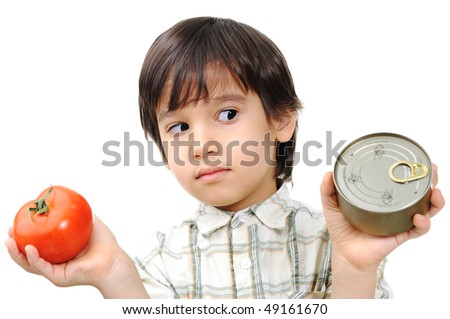 Kid between vegetables and aluminium can - dilemma - stock photo