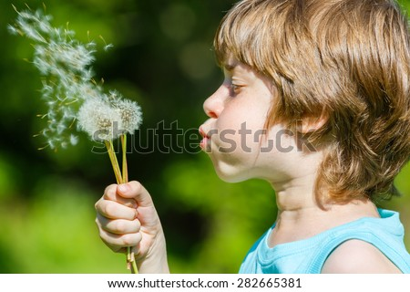 Kid blowing dandelion outdoor on sky background
