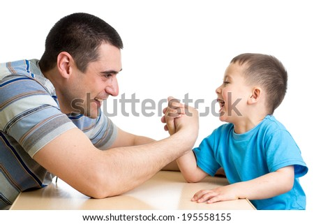 kid boy and his dad competing in physical strength - stock photo
