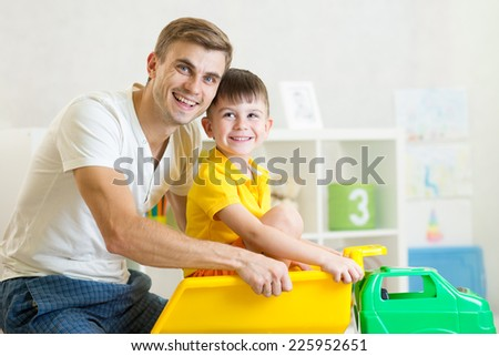 kid boy and his dad playing with toy trunk - stock photo