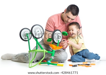 kid boy and his daddy fixing children bike