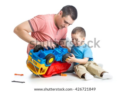 kid boy and his daddy fixing toy trunk - stock photo