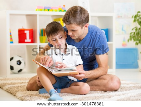 kid boy and his father read a book on floor indoors - stock photo