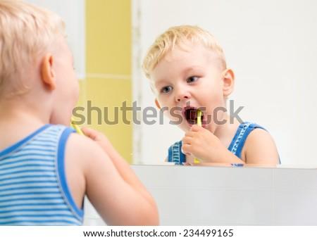 kid boy brushing teeth and looking at mirror - stock photo