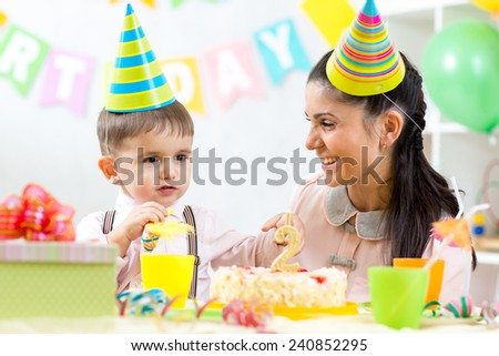 Kid boy celebrating his birthday holiday. Mother looking happily to her little son - stock photo