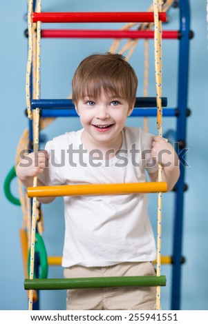 Kid boy climbing a rope ladder at home - stock photo