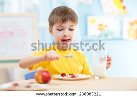 kid boy eating healthy food at home or nursery - stock photo