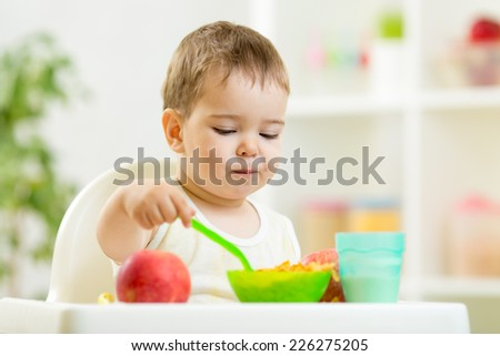 kid boy eating healthy food on kitchen - stock photo