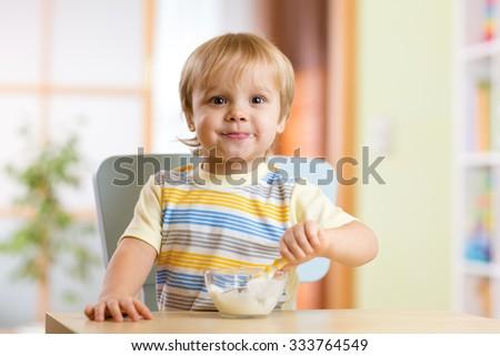 kid  boy eats healthy food at nursery room - stock photo