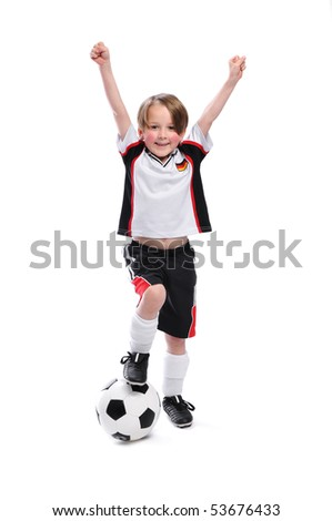 Kid / Boy in complete german soccer outfit raises his arms. He is the winner. - stock photo
