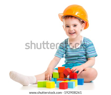 kid boy in hard hat with colorful building blocks - stock photo
