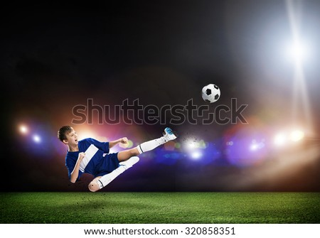 Kid boy kicking soccer ball at stadium field