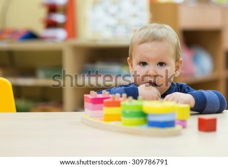 kid boy playing at home or play-school - stock photo