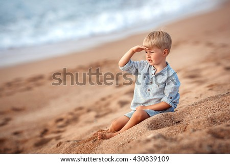 Kid boy playing on the beach. Sitting on the send.