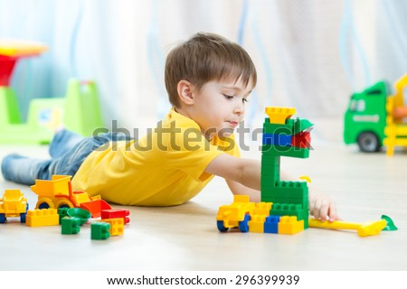 kid boy playing toy blocks on floor at home - stock photo