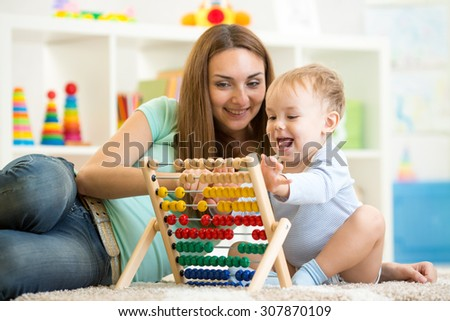 kid boy playing with abacus indoor at home - stock photo