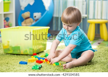 kid boy playing with building blocks at home or kindergarten
