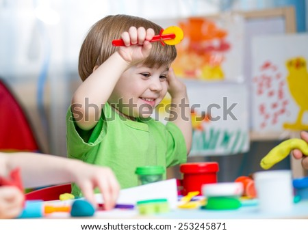 kid boy  playing with play clay at home or  play-school - stock photo