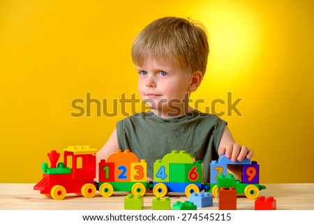 Kid boy plays toys on the table at nursery