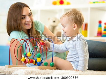 Kid boy plays with educational toy in nursery at home. Happy mother looking at her smart son. - stock photo