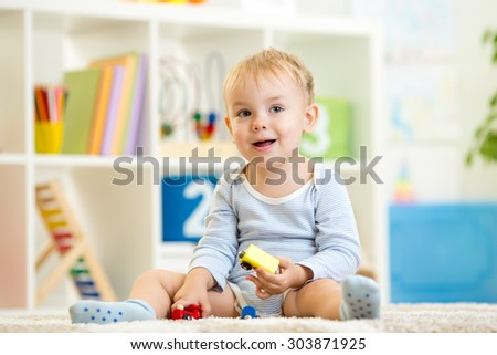 kid boy toddler playing toys at home - stock photo
