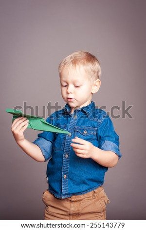 Kid boy 3-4 year old holding paper plane over gray. Wearing trendy clothes in room. Childhood. Vintage frame.  - stock photo