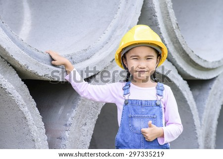 Kid civil engineer inspecting huge concrete pipe and make a thumb up