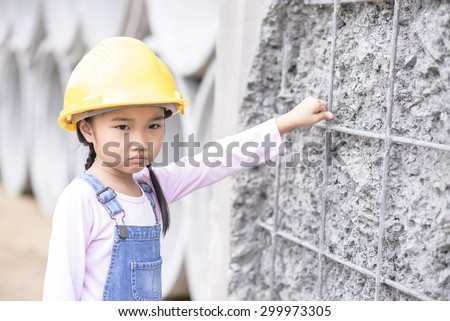 Kid civil engineer inspecting wire mesh on huge concrete pipe wall with bored mood