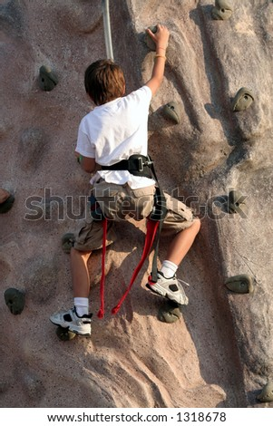 Kid climbing wall - stock photo