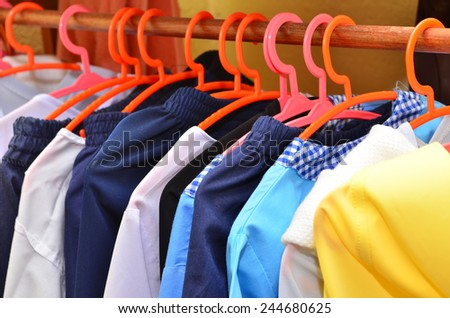 kid clothes of different colors on plastic hanger - stock photo