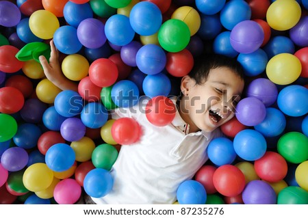Kid, colors, ball - playing in many colorful balls - stock photo
